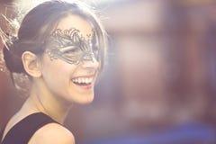 有黑化妆舞会面具的愉快的少妇 图库摄影