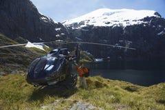 有直升机的远足者在山上面 库存照片