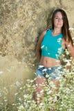 有直发倾斜在墙壁的穿戴蓝色顶面衬衣和斜纹布的逗人喜爱的女孩 图库摄影