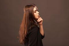 有头发卷曲的尾巴的美丽的深色的女孩 免版税图库摄影