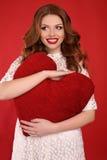 有黑发和明亮的构成的美丽的女孩,在庄重装束在手上的拿着大红色心脏 图库摄影