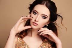 有黑发和明亮的构成的美丽的肉欲的妇女,与珠宝 图库摄影