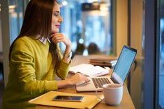 有黑发和黄色毛线衣的美丽的女商人在coworking工作并且释放无线连接 免版税库存照片