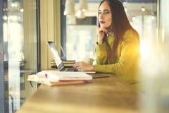 有黑发和黄色毛线衣的美丽的女商人在coworking工作 免版税库存图片