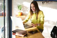 有黑发和黄色毛线衣的美丽的女商人在coworking的reating的文章上工作关于新书 库存图片