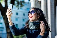 有黑发和laughting的太阳镜的美丽的十几岁的女孩采取selfies和-近景 免版税库存图片