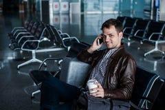 有黑发工作的,在椅子事的开会英俊的年轻人在等待他的飞行的机场 图库摄影