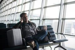 有黑发工作的,在椅子事的开会英俊的年轻人在等待他的飞行的机场 免版税库存图片
