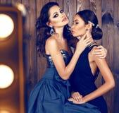 有黑发的两名美丽的妇女在豪华礼服 图库摄影