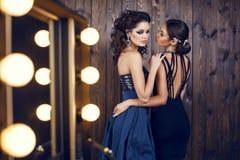 有黑发的两名美丽的妇女在豪华礼服 库存图片