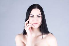 有黑发的妇女用手微笑和接触她的面颊的 被设色的背景秀丽蓝色概念容器装饰性的深度详细资料域充分的仿效宏观自然超出珍珠浅天空 免版税库存图片
