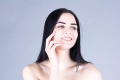 有黑发的妇女用手笑和接触她的面颊的 被设色的背景秀丽蓝色概念容器装饰性的深度详细资料域充分的仿效宏观自然超出珍珠浅天空 免版税库存图片