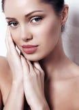 有黑发的妇女以自然构成和发光健康剥皮摆在 免版税库存图片