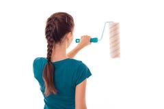 有黑发的少妇在uniforl在白色背景做与漆滚筒的整修在她的被隔绝的手上 免版税库存图片