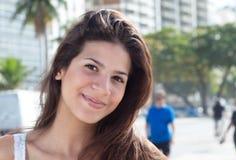 有黑发的微笑的妇女在城市 免版税库存照片