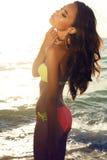 有黑发的性感的女孩在摆在日落海滩的明亮的比基尼泳装 库存照片