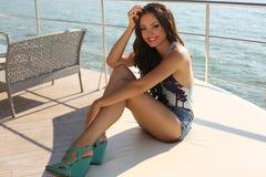 有黑发的性感的女孩在放松在游艇的典雅的泳装 图库摄影