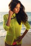 有黑发的性感的女孩在明亮的摆在海滩的衬衣和比基尼泳装 库存图片