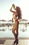 有黑发的性感的妇女在摆在与葡萄的泳装 免版税库存图片