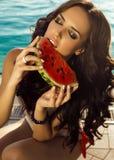有黑发的性感的妇女在泳装吃西瓜的 免版税库存照片