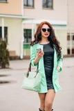 有黑发的惊人的美丽的女孩 时尚提包,长的外套薄菏颜色 时髦的太阳镜 红色肥满嘴唇 图库摄影