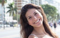 有黑发的愉快的笑的妇女在城市 免版税库存照片