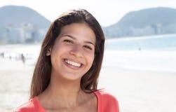 有黑发的愉快的笑的妇女在海滩 免版税库存照片