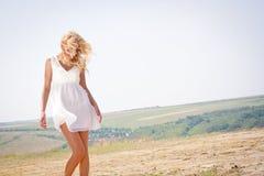 有头发的白肤金发的是妇女和的sundress吹的风 免版税库存图片