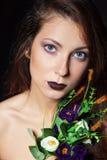有黑发的美丽的女孩和与紫色花花束的明亮的构成在黑背景的演播室 免版税库存照片