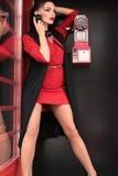 有黑发的美丽的女孩走由街道,红色电话b的 免版税库存照片