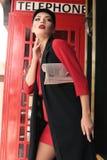 有黑发的美丽的女孩走由街道,红色电话b的 免版税图库摄影