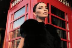 有黑发的美丽的女孩走由街道,红色电话b的 免版税库存图片