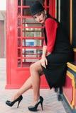 有黑发的美丽的女孩走由街道,红色电话b的 库存照片