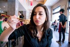 有黑发的美丽的女孩,穿戴在黑色拿着与筷子的肉馄饨 库存图片