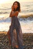 有黑发的美丽的妇女在摆在日落海滩的庄重装束 免版税库存图片