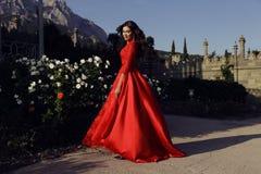 有黑发的美丽的妇女穿豪华红色礼服 免版税库存图片