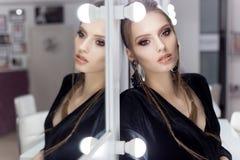 有头发的美丽的性感的女孩仿照岩石样式在镜子附近站立在一件黑天鹅绒褂子的化装室有brigh的 免版税库存照片