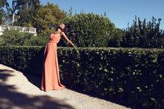 有黑发的美丽的混血儿女孩穿有珠宝的典雅的珊瑚礼服,摆在滑稽的宫殿旁边 免版税图库摄影