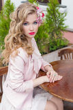 有头发的美丽的甜女孩和构成上色明亮的开会在桌上在一个室外咖啡馆和等待您的顺序 免版税库存照片