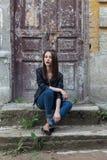 有黑发的美丽的逗人喜爱的时尚女孩有在一件皮革黑夹克的太阳镜的坐台阶门廊老 免版税图库摄影
