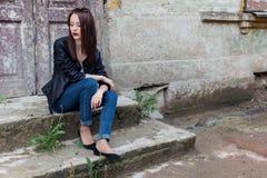 有黑发的美丽的逗人喜爱的时尚女孩有在一件皮革黑夹克的太阳镜的坐台阶门廊老 库存照片