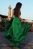 有黑发的肉欲的妇女在典雅的丝绸礼服 免版税库存照片
