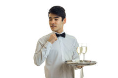 有黑发的迷人的英俊的年轻侍者调整他的拿着有两块玻璃的蝶形领结和手一个盘子 免版税库存照片