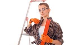 有黑发的年轻可爱的妇女在uniforl在白色背景做与工具的整修在她的被隔绝的手上 库存图片