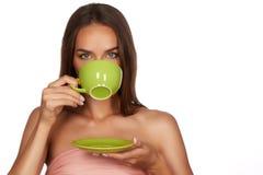 有黑发的年轻性感的美丽的妇女采摘了停滞一份陶瓷茶杯淡粉红的饮料茶或咖啡在白色后面 免版税库存照片