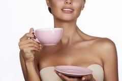 有黑发的年轻性感的美丽的妇女采摘了停滞一份陶瓷茶杯淡粉红的饮料茶或咖啡在白色后面 免版税库存图片
