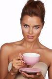 有黑发的年轻性感的美丽的妇女采摘了停滞一份陶瓷茶杯淡粉红的饮料茶或咖啡在白色后面 库存照片