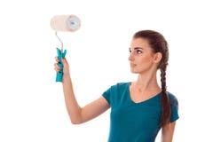 有黑发的年轻美丽的妇女在uniforl在白色做与漆滚筒的整修在她的被隔绝的手上 库存图片