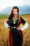 有黑发,绿色和红色天鹅绒的少妇 库存照片