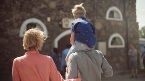 有他们可爱的儿子的年轻父母走和获得乐趣在庭院里 股票视频